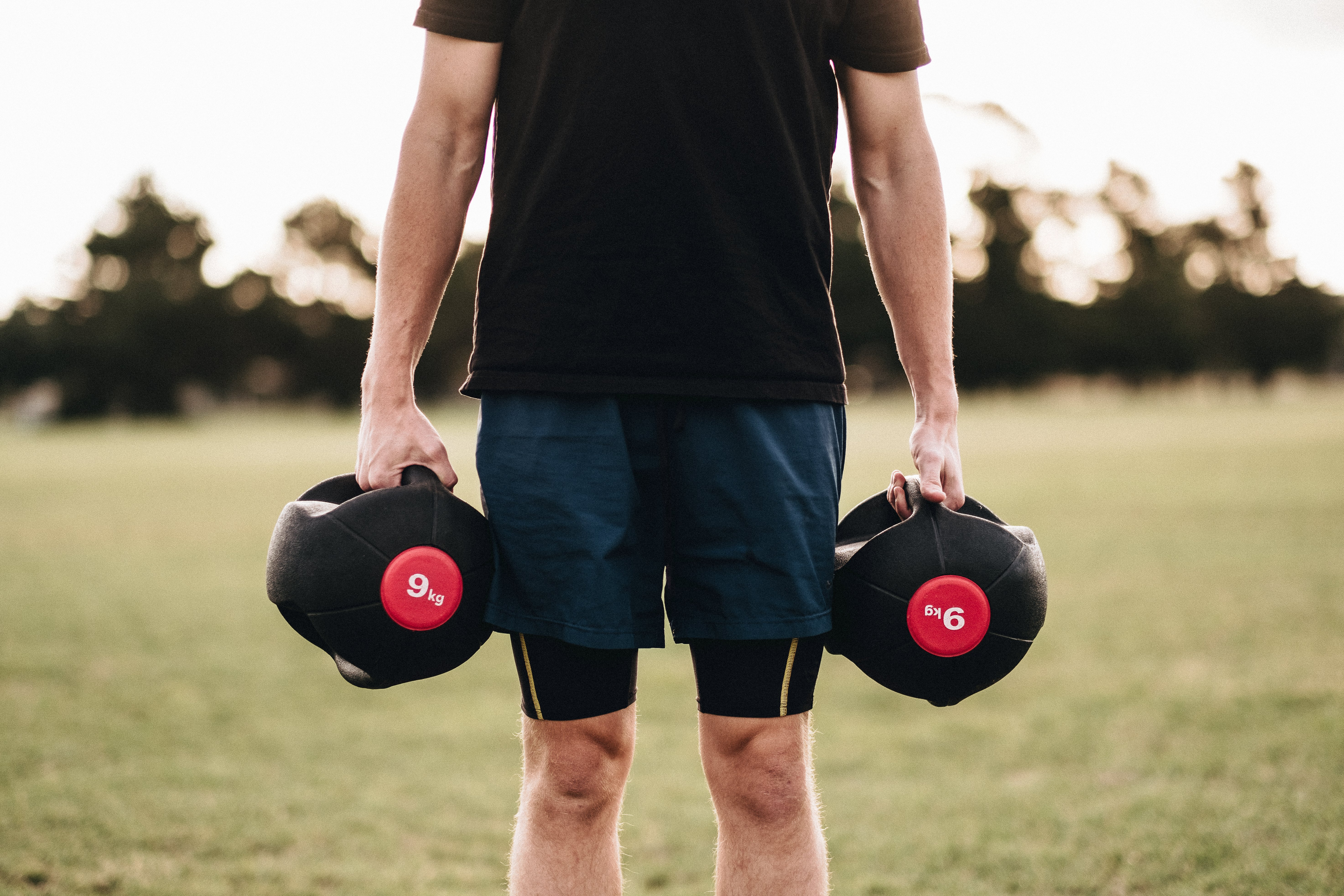 Canva - Person Holding Black Kettlebells