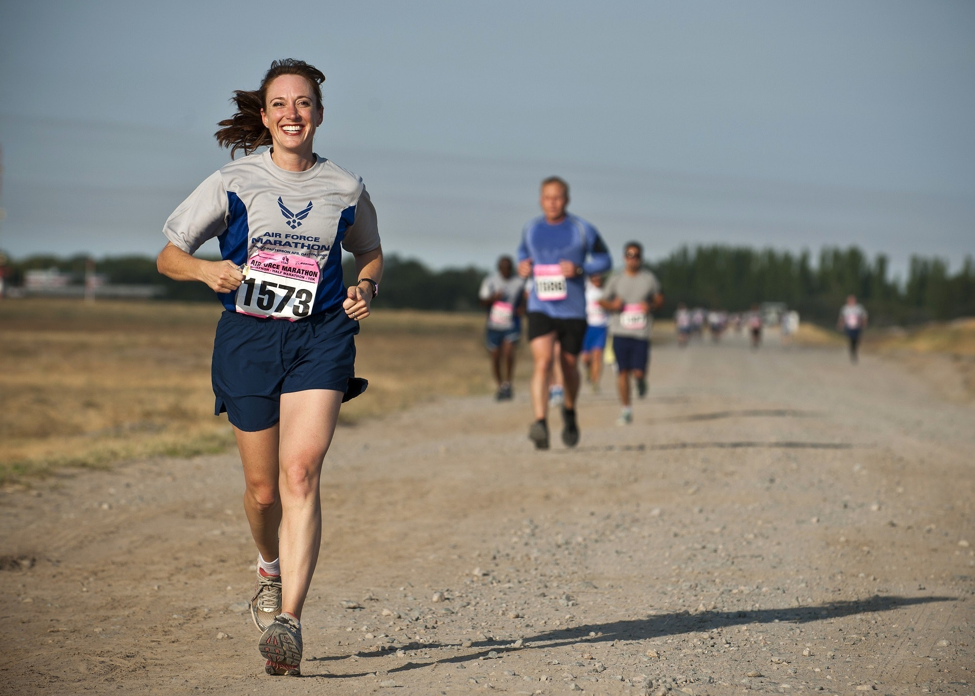 woman-in-gray-crew-neck-shirt-running-on-brown-soil-during-34495